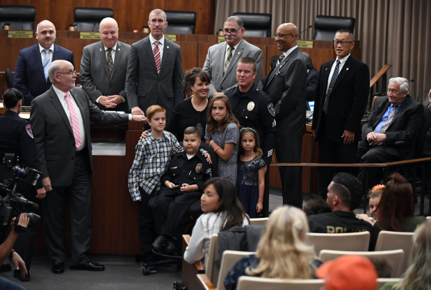 The Walker family, from left, Taryn, 10, James, 9, Giana, 6, Drake, 7, James and Leslie, is surrounded by city council members after Torrance PD Chief Eve Irvine swore in Drake Walker as an honorary police officer at the City Council meeting on Tuesday, October 16, 2018. Drake has wanted to be a police officer like his father, James, who is a sergeant with the Torrance Police Department, but was diagnosed recently with an aggressive, inoperable tumor at the base of his brain stem.  (Photo by Axel Koester, Contributing Photographer)
