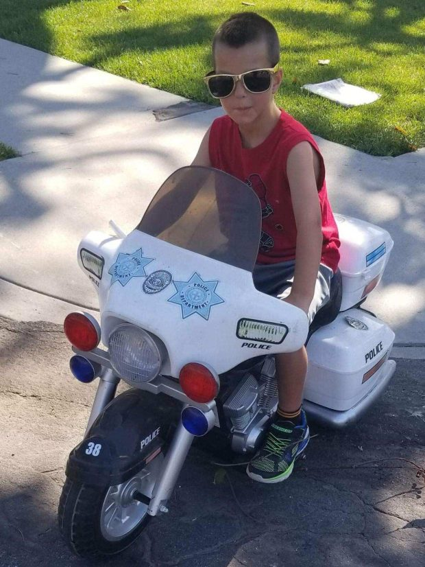 After his first five-day hospital stay in July 2018, 7-year-old Drake Walker immediately hops on his police motorcycle and heads out for patrol after returning home. (Courtesy of Leslie Walker)